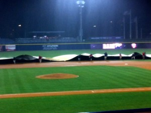 The grounds crew covers the infield at First Tennessee Park.